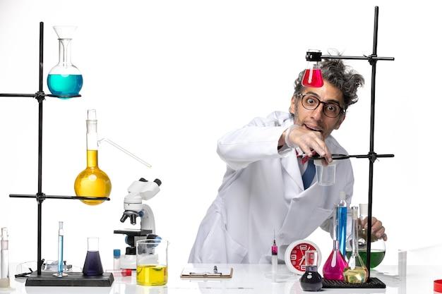 さまざまなソリューションで作業している医療スーツの正面図男性科学者