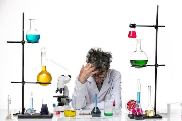 Вид спереди ученый-мужчина в медицинском костюме, работающий с решениями, чувствуя усталость