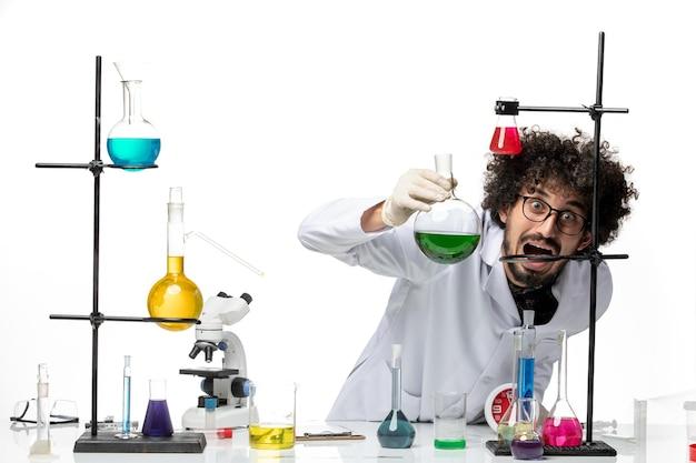 Вид спереди ученый-мужчина в медицинском костюме, работающий с растворами на белом пространстве
