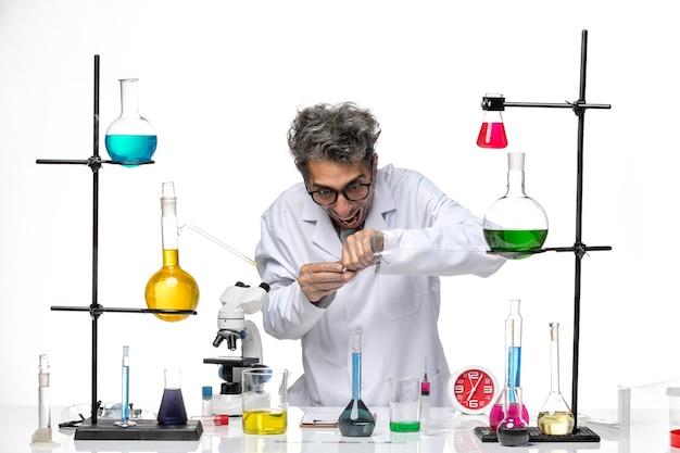 Вид спереди ученый-мужчина в медицинском костюме, работающий с растворами