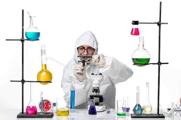 ソリューションとテーブルの周りの特別な防護服の正面図男性科学者