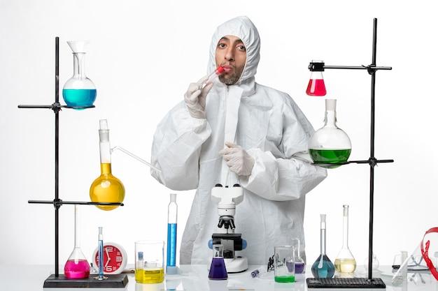 空のフラスコを保持している特別な防護服の正面図男性科学者