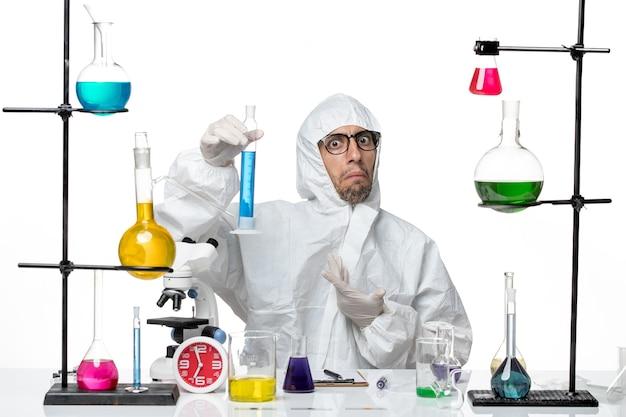 파란색 솔루션으로 플라스크를 들고 특수 보호 복에 전면보기 남성 과학자