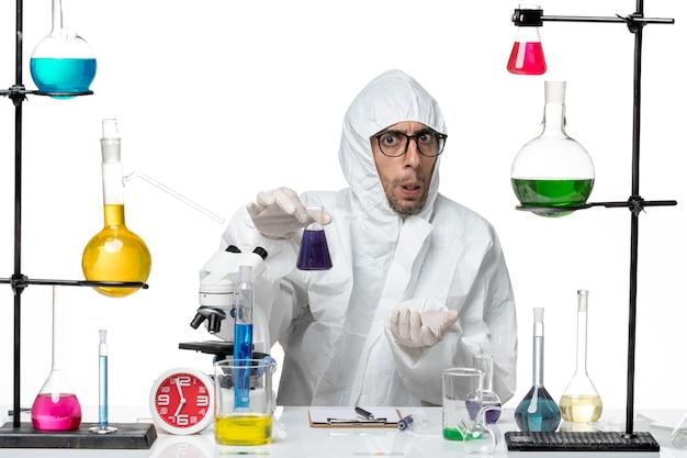 Вид спереди ученый-мужчина в специальном защитном костюме, держащий фляжку с фиолетовым раствором