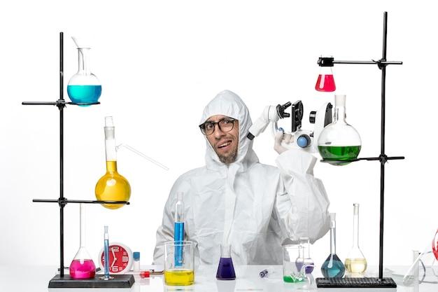 顕微鏡を保持している特別な防護服の正面図男性科学者