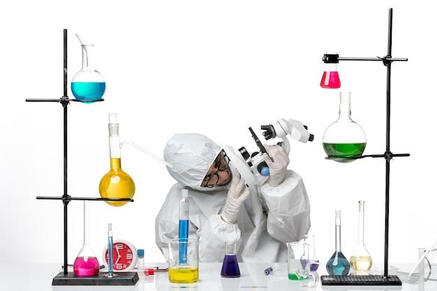 Вид спереди ученый-мужчина в специальном защитном костюме с микроскопом