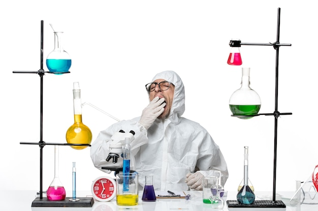 机の周りに座っている特別な防護服を着た正面図の男性科学者が、あくびをするのに疲れを感じています。
