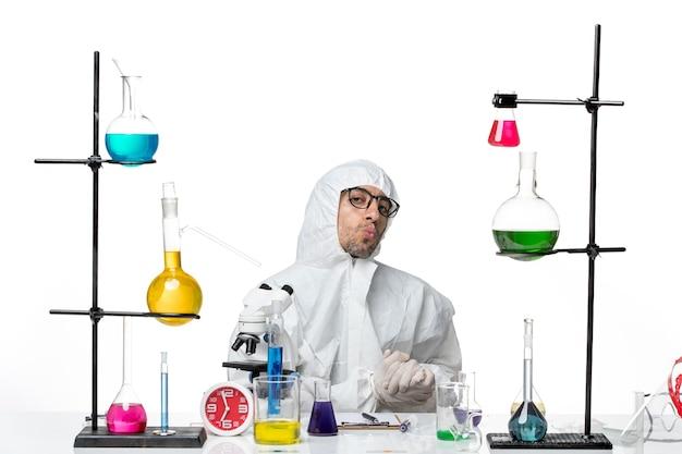 ソリューションと机の周りに座っている特別な防護服の正面図男性科学者