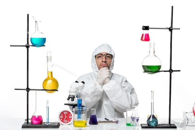솔루션과 함께 책상 주위에 앉아 특수 보호 복에 전면보기 남성 과학자