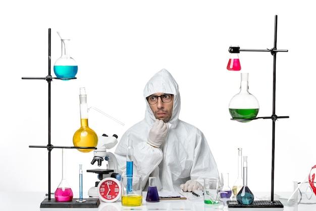 解決策を考えてテーブルの周りに座っている特別な防護服の正面図男性科学者