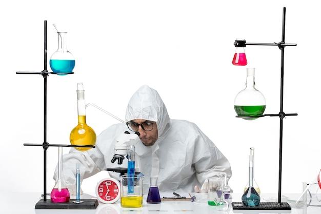 ソリューションとテーブルの周りに座っている特別な防護服の正面図男性科学者