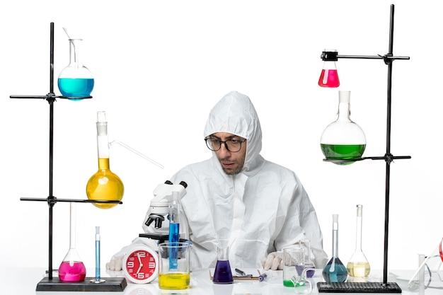 솔루션 테이블 주위에 앉아 특수 보호 복에 전면보기 남성 과학자
