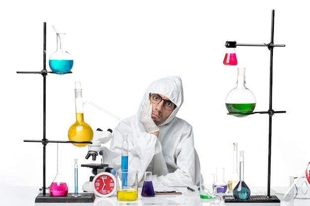 さまざまなソリューションで座っている特別な防護服の正面図男性科学者