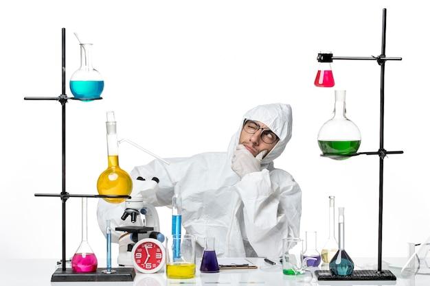 解決策と考えて座っている特別な防護服の正面の男性科学者