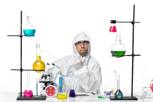 解決策を押し下げて座っている特別な防護服を着た正面図の男性科学者