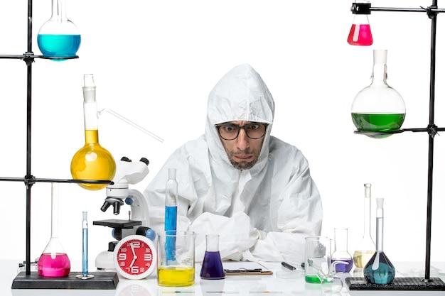 Вид спереди ученый-мужчина в специальном защитном костюме сидит с решениями, думая