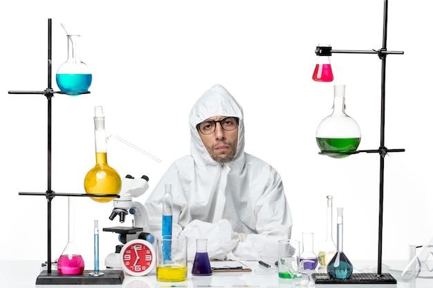 Вид спереди ученый-мужчина в специальном защитном костюме, сидящий с растворами