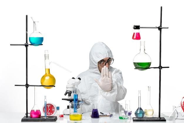 Вид спереди ученый-мужчина в специальном защитном костюме сидит