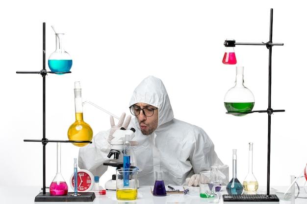 座っている特別な防護服の正面図男性科学者