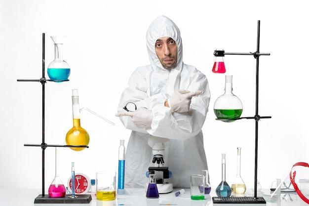 ソリューションとテーブルの周りに立っている特別な防護服の正面図男性科学者