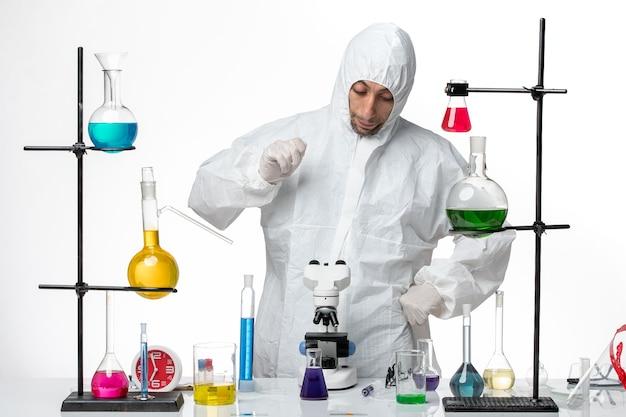 ソリューションを扱う特別な防護服を着た正面図の男性科学者