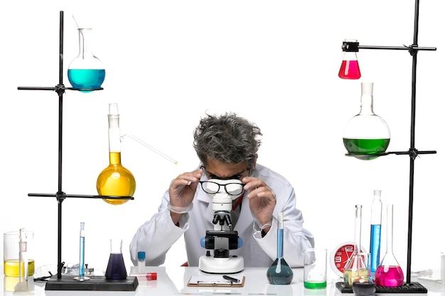 彼のサングラスをチェックしている白い医療スーツの正面図の男性科学者