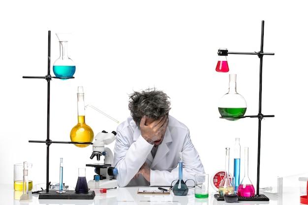 Вид спереди ученый-мужчина в белом медицинском костюме, чувствуя себя таким измученным