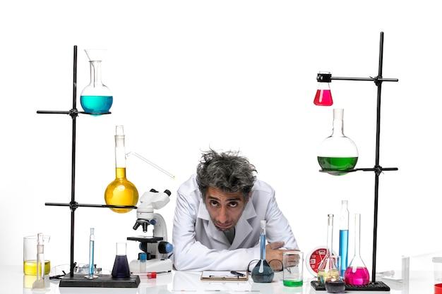 Вид спереди ученый-мужчина в белом медицинском костюме, чувствуя себя таким усталым