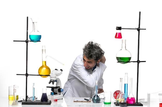 솔루션 테이블 앞의 흰색 의료 소송에서 전면보기 남성 과학자