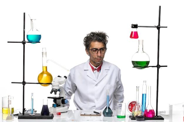 Вид спереди ученый-мужчина в белом медицинском костюме, глядя на что-то
