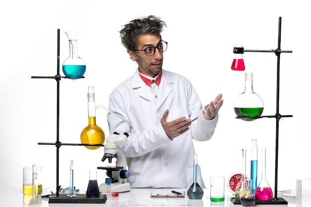 Вид спереди ученый-мужчина в белом медицинском костюме, стоящий перед столом с растворами