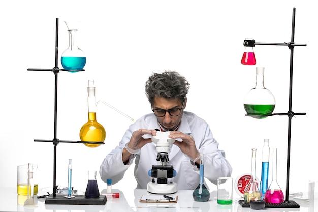 현미경을 사용하여 흰색 의료 소송에서 전면보기 남성 과학자