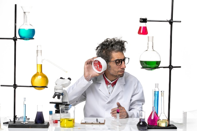 Front view male scientist in medical suit holding clocks on light-white background chemistry covid lab virus health