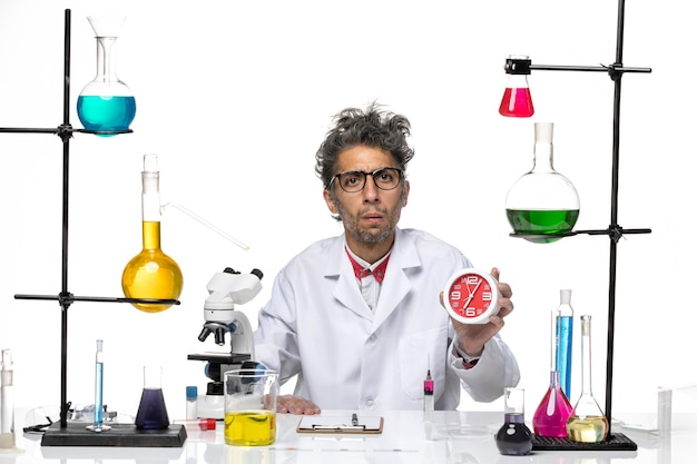 Front view male scientist in medical suit holding clocks on white background chemistry health covid- lab virus