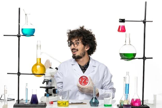 Scienziato maschio di vista frontale in vestito medico che tiene gli orologi rossi sullo spazio bianco chiaro