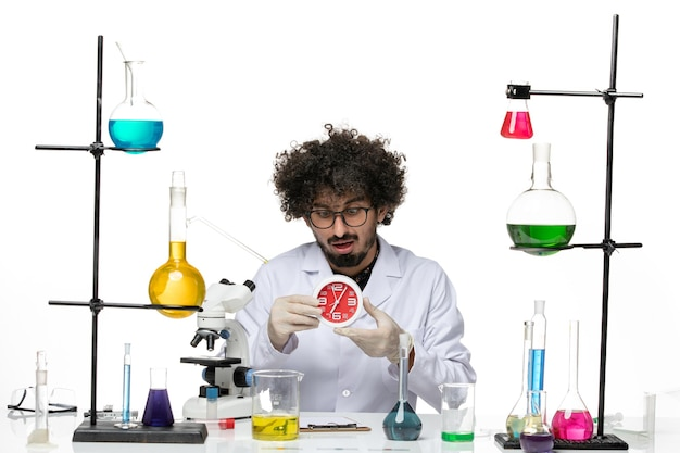Front view male scientist in medical suit holding red clocks on light white space