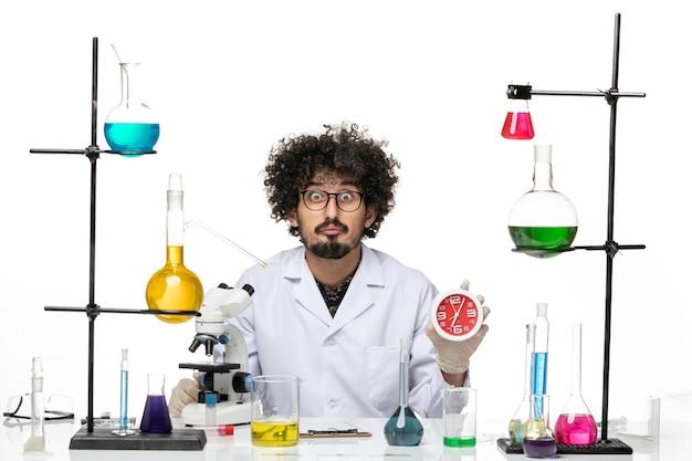Scienziato maschio di vista frontale in vestito medico che tiene gli orologi rossi su spazio bianco