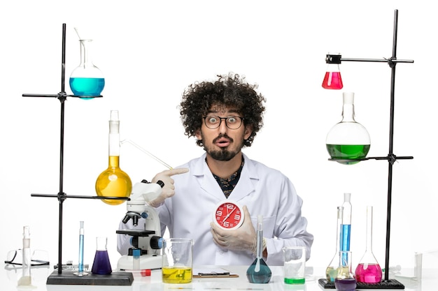 Front view male scientist in medical suit holding red clocks on the white space
