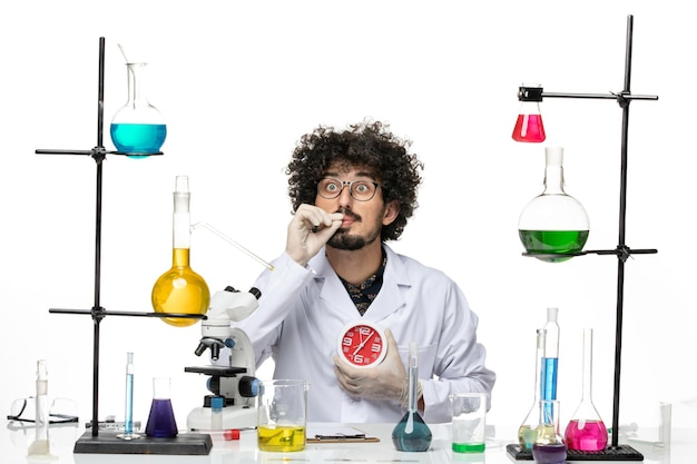 Front view male scientist in medical suit holding red clocks on white space