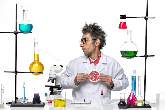Front view male scientist in medical suit holding round clocks on white background chemistry health covid- lab virus