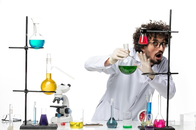 Front view male scientist in medical suit holding solutions on white space