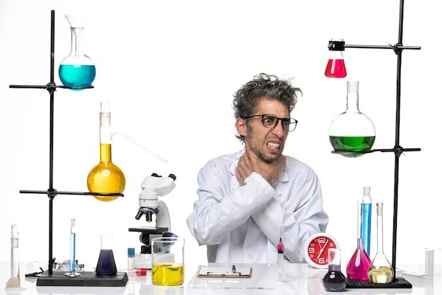 Scienziato maschio vista frontale in tuta medica seduto e soffocamento se stesso su sfondo bianco chimica covid laboratorio virus salute
