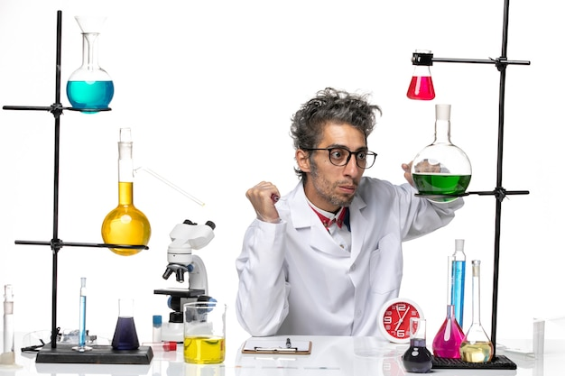 Scienziato maschio di vista frontale in vestito medico che si siede davanti al tavolo con soluzioni su chimica di salute del virus del laboratorio covid scrivania bianca