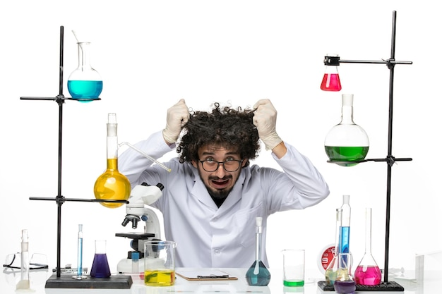 Front view male scientist in medical suit sitting and tearing his hair on white space