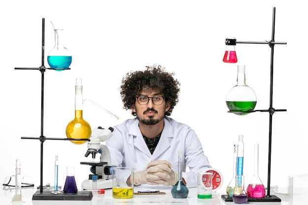 Front view male scientist in medical suit sitting with solutions and microscope on white desk