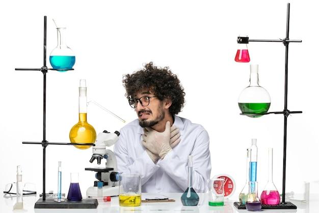 Scienziato maschio di vista frontale in vestito medico che si siede con soluzioni e microscopio su uno spazio bianco