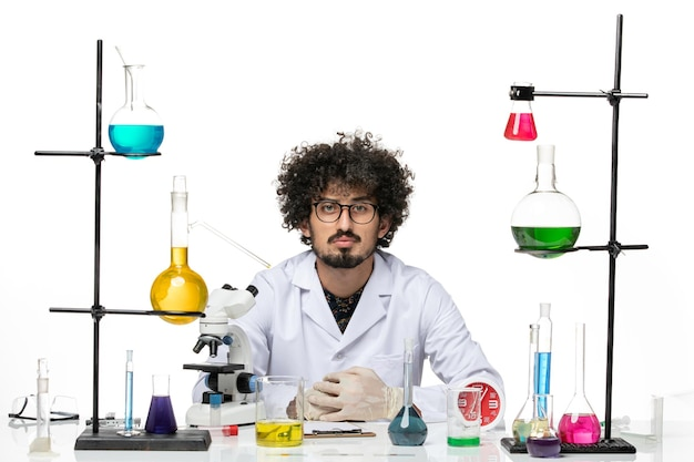 Front view male scientist in medical suit sitting with solutions and microscope on a white space