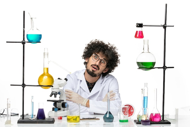 Front view male scientist in medical suit sitting with solutions and microscope on the white space