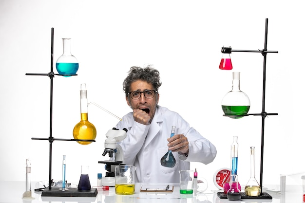 Front view male scientist in medical suit using microscope holding blue solution on white background lab health virus coronavirus