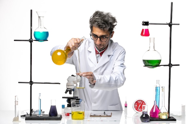 Front view male scientist in medical suit working with different solutions on a white background covid- lab virus health chemistry